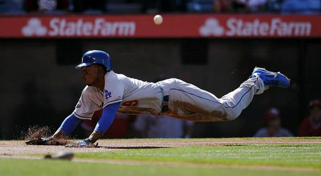 Dee Gordon scores after a throwing error by Angels first baseman Albert Pujols. Gordon was involved in all three Dodger scoring plays in their 3-1 win of the Angels on Saturday. (Photo by Juan Ocampo)
