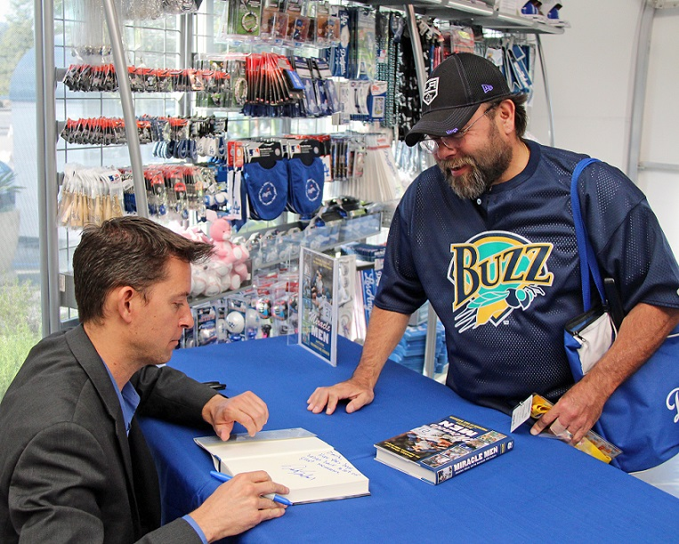 Josh Suchon signs a copy of his new book Miracle Men for longtime Dodgers (and Kings) season ticket holder David Baltazar of Long Beach. (Photo credit - Ron Cervenka)